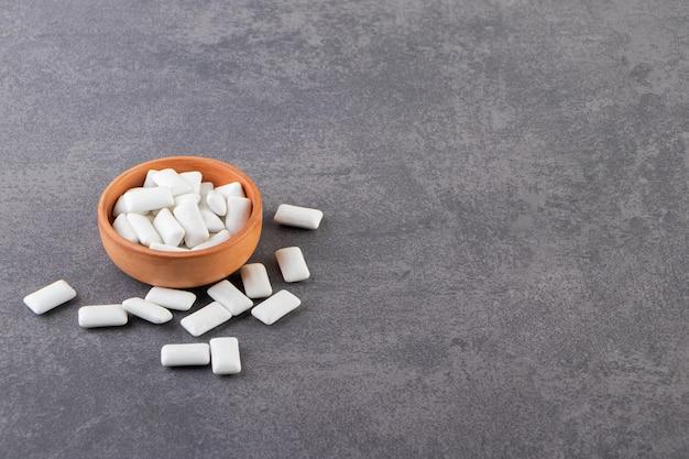 Gomas brancas em fundo cinza e na tigela.