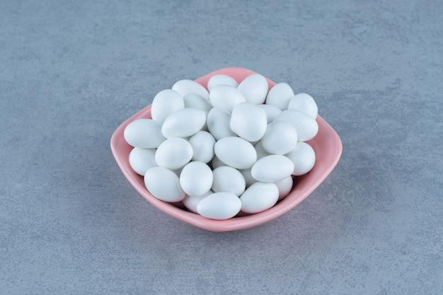 Gomas brancas na tigela, na mesa de mármore.