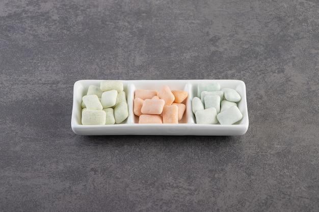 Gomas doces no prato sobre superfície cinza