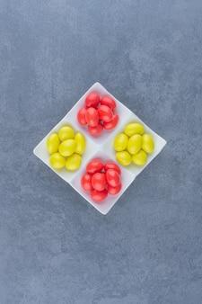 Gomas forradas no prato, no fundo de mármore.