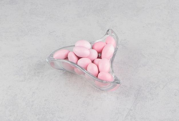 Gomas rosa na tigela na superfície do mármore