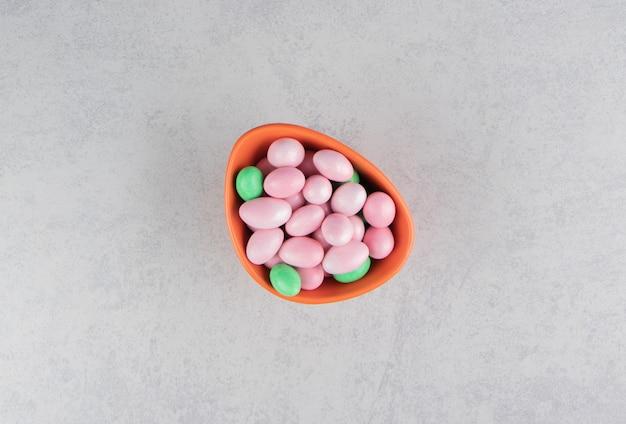 Gomas verdes e rosa na tigela na superfície do mármore