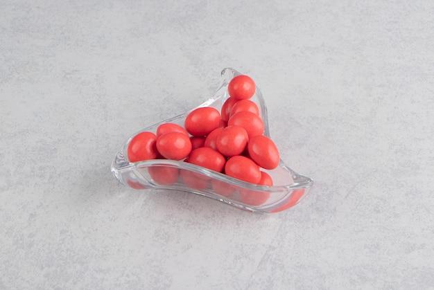 Gomas vermelhas na tigela na superfície do mármore