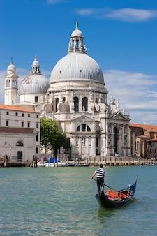 Gôndola no canal grande com a basílica di santa maria della salute ao fundo, veneza, itália