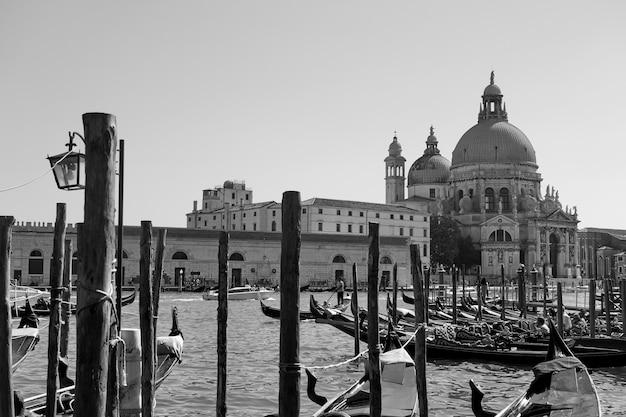 Gôndolas e a igreja de santa maria della salute, do outro lado do grande canal, em veneza, itália. vista da cidade em preto e branco veneziana