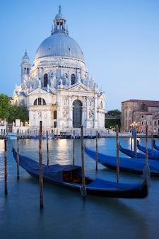 Gôndolas no canal grande com a basílica di santa maria della salute ao fundo, veneza, itália