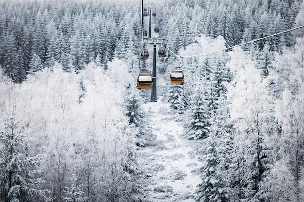 Gôndolas sobe nas montanhas, estação de esqui, coberta de neve. paisagem de inverno