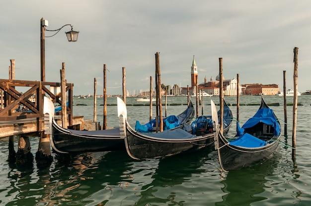 Gôndolas venezianas tradicionais flutuando na água em lagoa na ilha de san giorgio