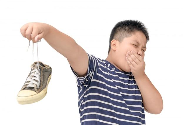 Gordo nojo segurando um par de sapatos fedorentos