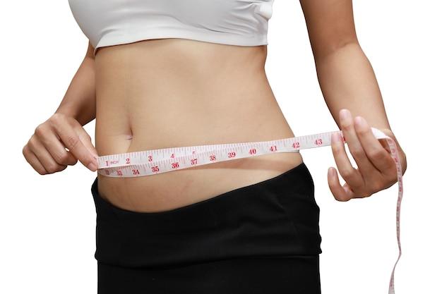 Gordura corporal de mulher em close-up usando fita métrica de estômago isolado e fundo branco com traçado de recorte