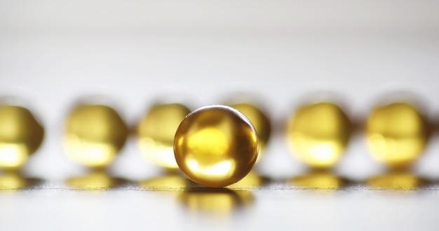 Gordura de peixe. produtos médicos para o tratamento de doenças. o conceito de dependência de saúde em comprimidos. cápsulas de óleo de peixe em fundo de madeira. Foto Premium