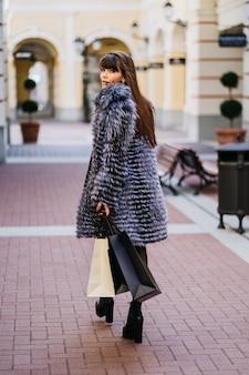 Gorgeus, morena sorridente, com cabelos longos e lisos, vestindo um casaco de pele e a saia branca de pé no contexto do edifício de estilo clássico, com as sacolas de compras