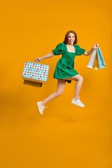 Gostando de comprar feliz alegre elegante senhora segurando muitos pacotes de compras pulando linda senhora j ...