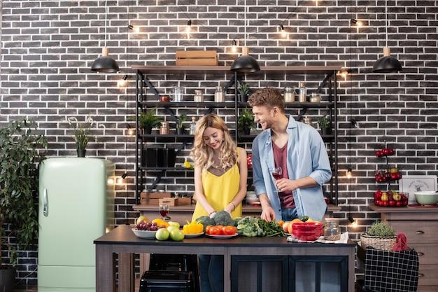Gostando de cozinhar. linda mulher loira e feliz com cabelos ondulados, aproveitando o tempo para cozinhar com seu homem
