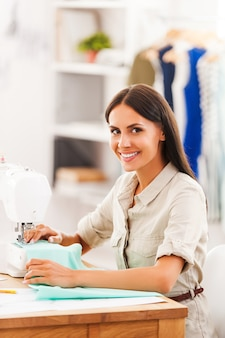 Gostando de seu trabalho criativo. vista lateral de uma jovem sorridente costurando enquanto está sentada em seu local de trabalho na oficina de moda