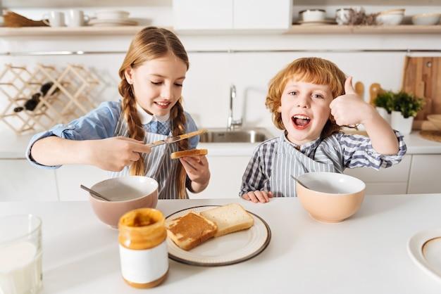 Gostando de sua comida. menina doce e carinhosa fazendo um sanduíche com manteiga de amendoim para seu irmão mais novo, enquanto os dois estão sentados à mesa e seu irmão parece animado