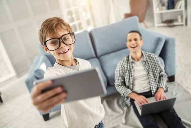 Gosto de fotografar. bonito, alegre, feliz, louro, sorrindo, usando óculos grandes e tirando selfies enquanto seu pai está sentado ao fundo