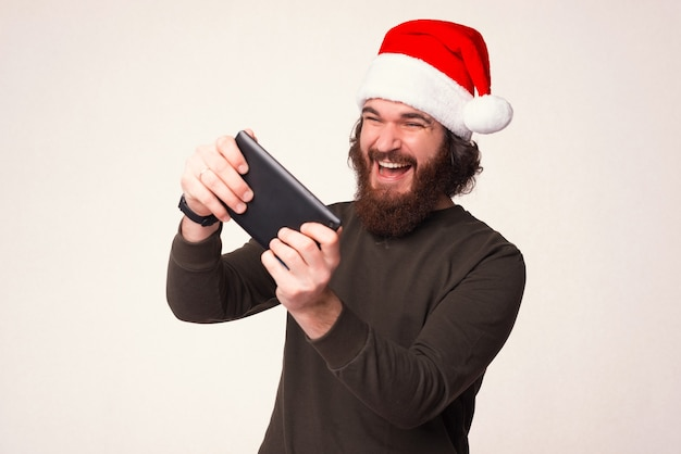 Gosto do meu novo tablet, especialmente de jogar nele. homem barbudo joga animado enquanto ele está usando chapéu de natal.