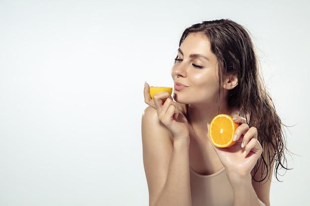Gosto. mulher jovem e bonita com fatias de frutas cítricas perto do rosto em branco.