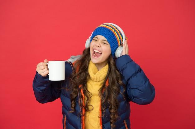Gosto musical. o fim de semana começa assim. tendência da moda hipster. atividade de férias de inverno. sentindo-se aquecido e feliz. roupa elegante de criança sorridente alegre ouvir música. ouvir música e beber cacau.
