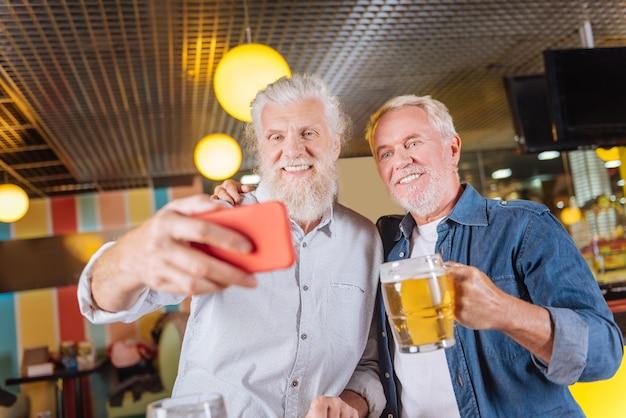 Gosto perfeito. homem barbudo simpático saboreando a cerveja enquanto descansa no bar