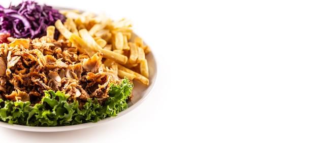 Gostoso kebab de frango turco preparado e servido no prato branco com lindos vegetais caseiros e batatas fritas salgadas.