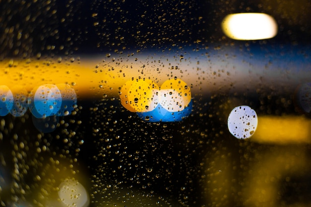 Gota d'água nas janelas e bokeh da cidade ao pôr do sol.