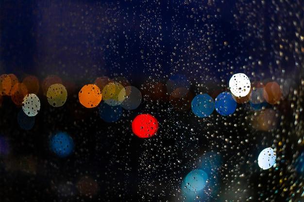 Gota de água no windows e bokeh da cidade no pôr do sol Foto Premium