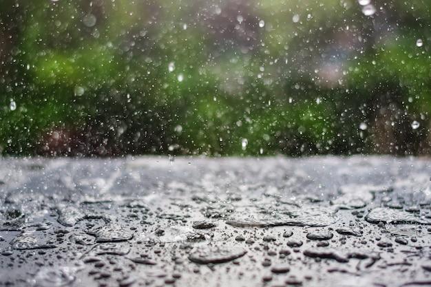 Gota de chuva caindo no quadro-negro com fundo verde da natureza