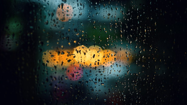 Gota de chuva na janela à noite. janela da sala de estar do condomínio ou apartamento na noite da estação chuvosa em bangkok, tailândia. a janela externa é o bokeh borrado da chuva da luz da cidade e da árvore e do céu naturais.