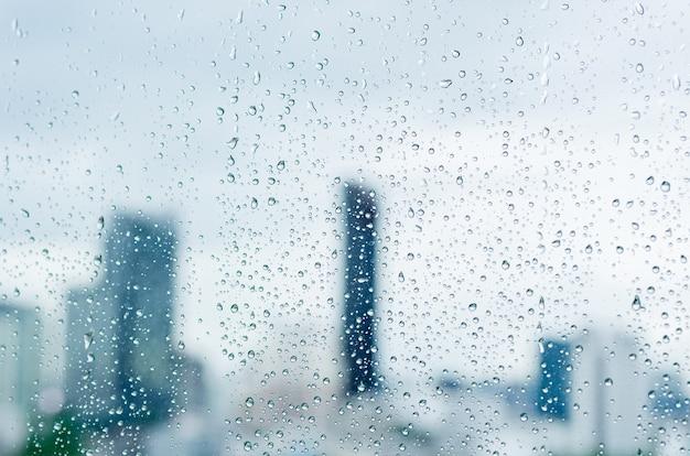 Gota de chuva na janela de vidro na hora do dia na temporada de monções com fundo de edifícios de cidade turva.