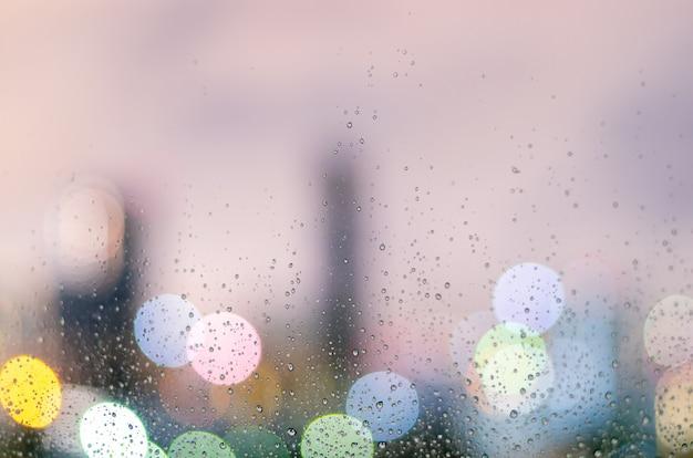Gota de chuva na janela de vidro na temporada de monções com bokeh colorido de fundo de prédios da cidade
