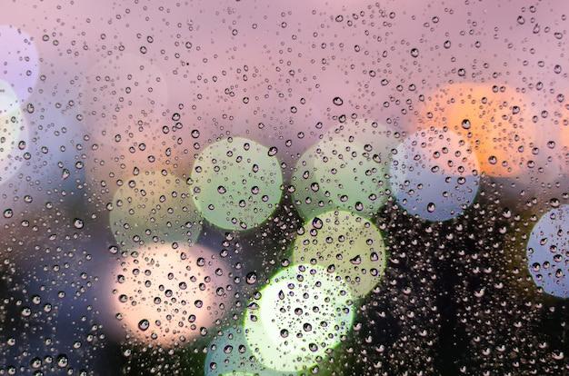 Gota de chuva na janela de vidro na temporada de monções com luz colorida bokeh de fundo de edifícios da cidade.