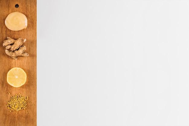 Gota de coalhada de limão com ingredientes na bandeja de madeira