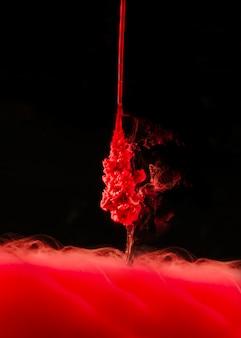 Gota vermelha brilhante que espirra na água