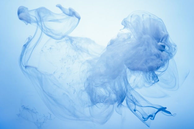 Gotas azuis brilhantes na água em um fundo branco