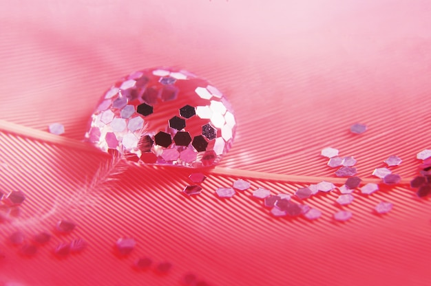 Gotas com brilhos em uma pluma rosa. foto artística bonita suave delicada do close-up. imagens macro abstrato brilhante.