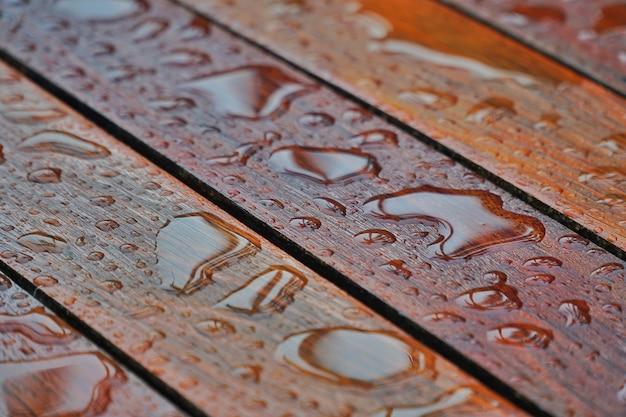 Gotas da água em uma superfície de assoalho de madeira. gota da água na madeira com pingo de chuva após uma chuva.