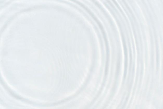 Gotas de água caem na superfície transparente da água à luz do sol. vista superior, configuração plana.