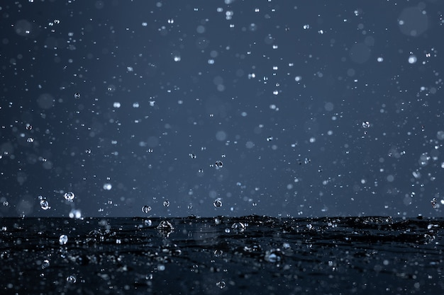 Gotas de água caindo em uma superfície preta