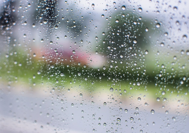 Gotas de água de chuva e texto na janela com resumo desfocagem o fundo