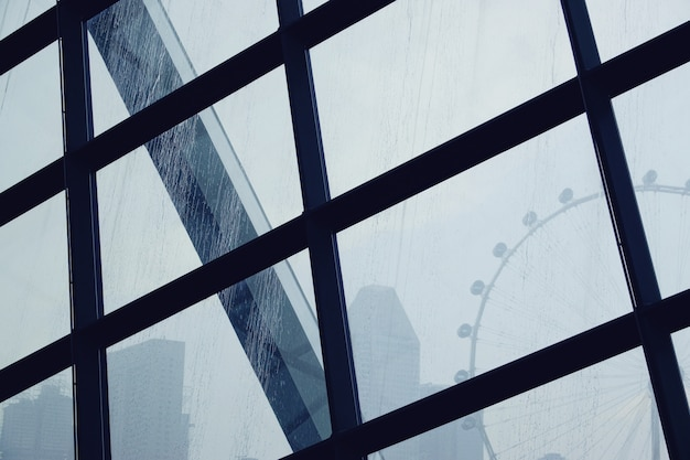 Gotas de água de chuva no vidro da janela com fundo de roda gigante