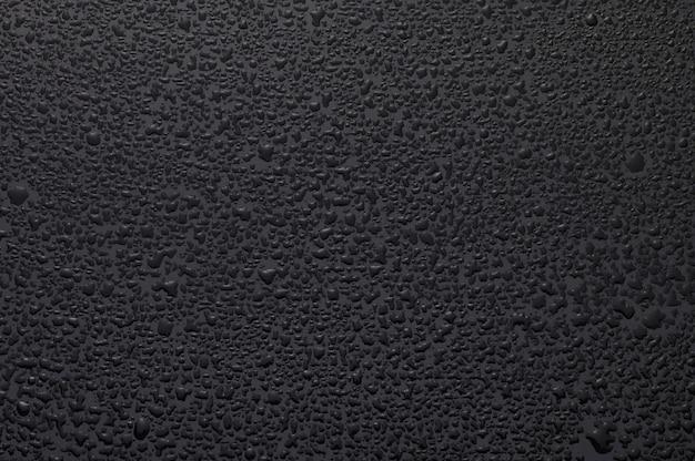 Gotas de água em vidro preto. fundo iluminado com li branco
