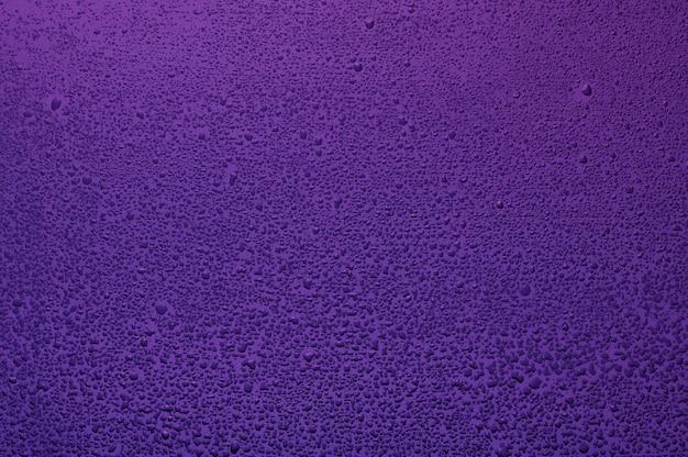 Gotas de água em vidro preto. fundo iluminado com lilás