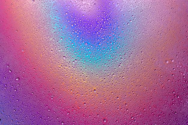 Gotas de água na superfície multicolorida. foto macro, gota, base de plástico de sombra.
