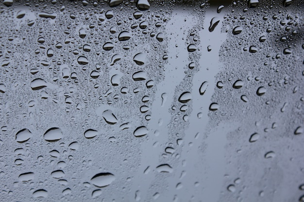 Gotas de água no copo. fundo das gotas da água que fluem abaixo do vidro.