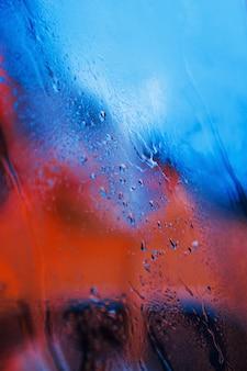 Gotas de água no fundo de vidro de néon. cores vermelho e azul