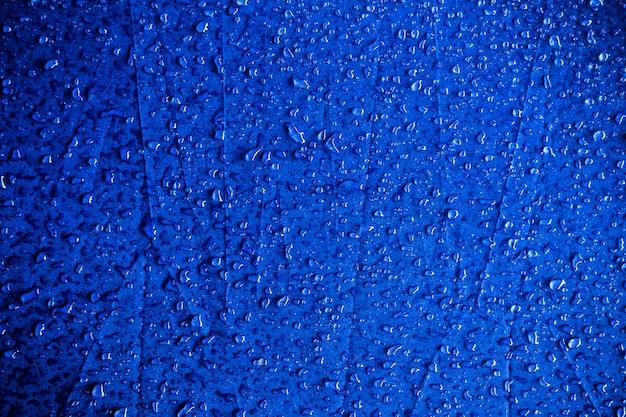 Gotas de água no tecido azul. gotas de água no fundo azul