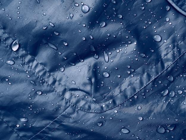 Gotas de água no tecido da membrana impermeável. visualização de detalhes da textura de um pano impermeável azul.