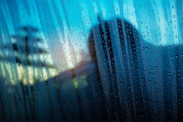 Gotas de água no vidro e sombras.